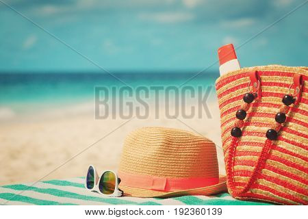 hat, sunglasses and bag with suncream on tropical beach