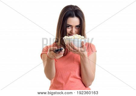 Pretty young girl eats pop-corn and watching tv isolated on white background