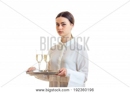 Beautiful brunette waitress in uniform holding a trey with wine isolated on white background