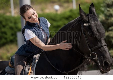 Beautiful smiling woman sitting on brown purebred horse