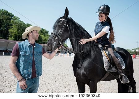 Handsome man in cowboy hat holding bridle and smiling young woman riding horse