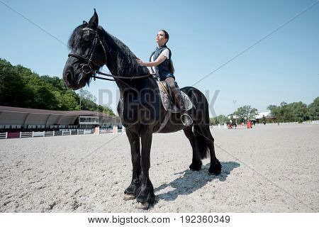 Confident young woman riding brown purebred horse