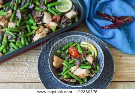Baked chicken breasts green beans mushrooms red cherry tomatoes sesame seeds and lemon slice in a small grey bowl. Healthy hot salad. Balanced eating and diet