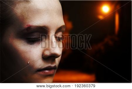 Crying woman harm harmed young adult background view