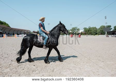Handsome young man in cowboy hat riding purebred brown horse