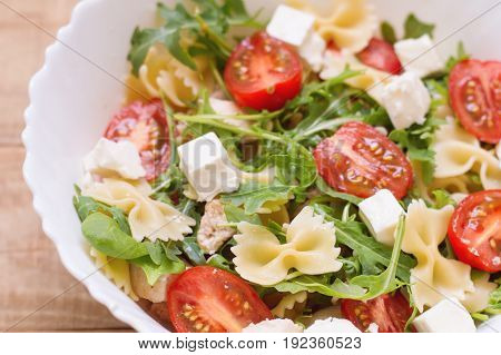 Big portion of homemade pasta salad with red cherry tomatoes feta cheese chicken breast baby spinach leaves arugula (rocket leaves) and farfalle. Appetizer. Healthy eating