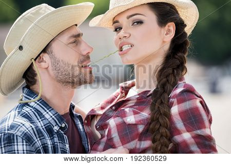 young passionate cowboy style couple embracing with straw