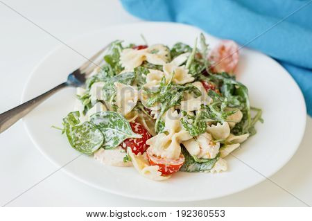 Portion of pasta salad with rucola leave baby spinach farfalle sliced cherry tomatoes and chicken meat dressed with white sauce and served on white plate with fork and blue napkin