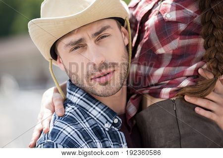young handsome cowboy embracing his girlfriend and looking at camera