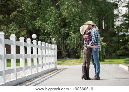 cowboy style couple kissing while spending time in park at daytime