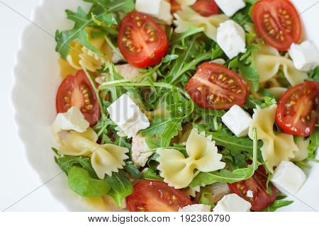 Pasta salad with farfalle cherry tomatoes rocket leaves spinach chicken meat and feta cheese in white bowl. Healthy salad. Balanced meal