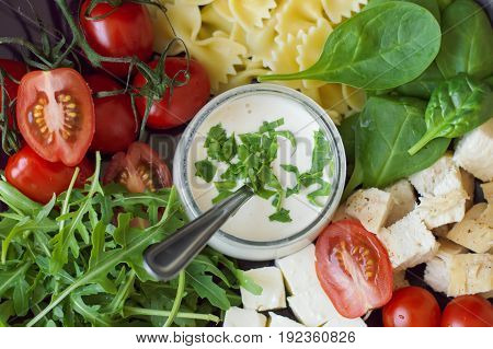 White mayonnaise sauce served with fresh rocket salad leaves red cherry tomatoes farfalle pasta baby spinach leaves feta cheese cubes and chicken meat. Top view. Salad dressing