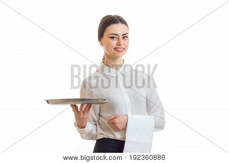Cheerful young waitress in uniform with trey in hands smiling isolated on white background