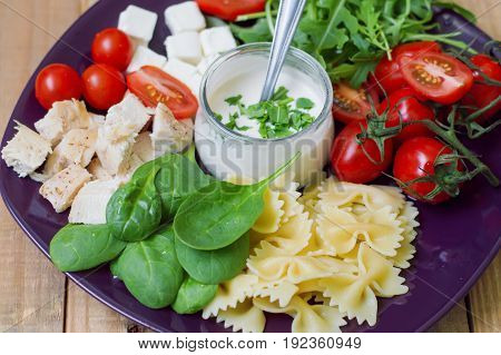 Mix of farfalle pasta baby spinach leaves cherry tomatoes chicken meat feta cubes rucola leaves and white mayo sauce