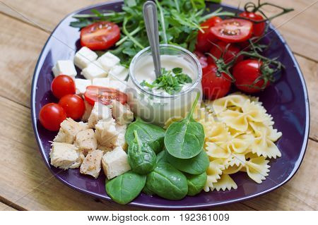 Portion of pasta salad with baby spinach italian farfalle chicken cubes red cherry tomatoes feta cheese and arugula served on a purple plate with white sauce. Healthy eating. Balanced diet concept