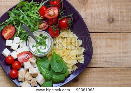 Background with fresh homemade pasta salad. Farfalle spinach leaves chopped chicken breast cherry tomatoes feta cubes rocket leaves and white sauce served on wooden table