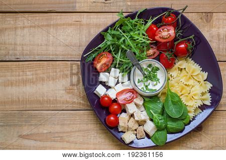 Pasta salad with farfalle red cherry tomatoes arugula feta cheese chicken meat and baby spinach served on a big plate with white sauce Balanced and healthy meal