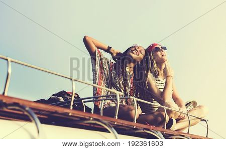 Women Sitting on The Roof of the Van Traveling Road Trip