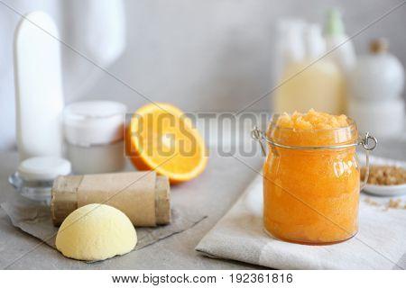 Glass jar with orange body scrub on napkin