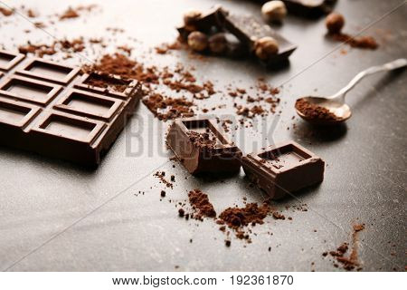 Broken chocolate pieces with spoon on table