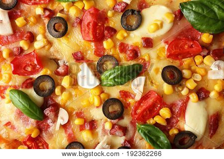Close up view of tasty pizza with pepperoni, mushrooms, tomatoes, black olives, corn and basil