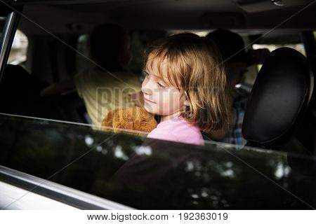 Young caucasian girl sit inside the car open window