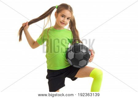 cutie little girl plays a football and looks at the camera isolated on white background