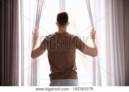 Young man opening curtains