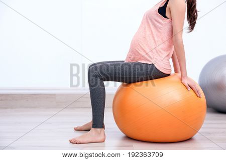 Beautiful pregnant woman doing exercise indoors