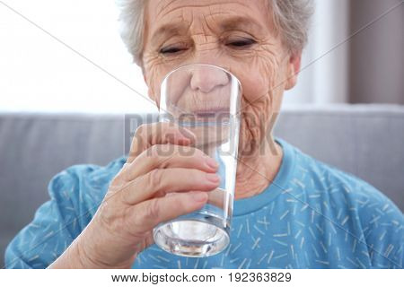 Elderly woman drinking water at home. Concept of retirement