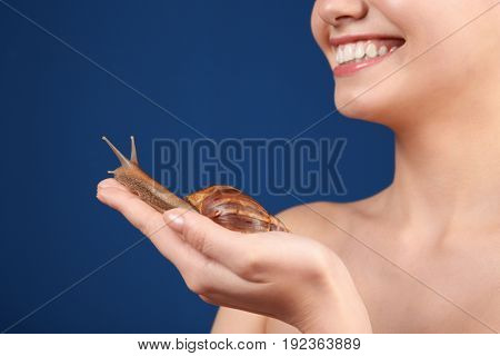 Beautiful young woman with giant Achatina snail on color background, closeup