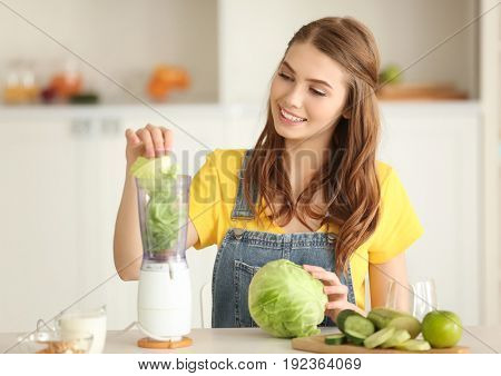 Weight loss concept. Beautiful young woman preparing green smoothie in kitchen