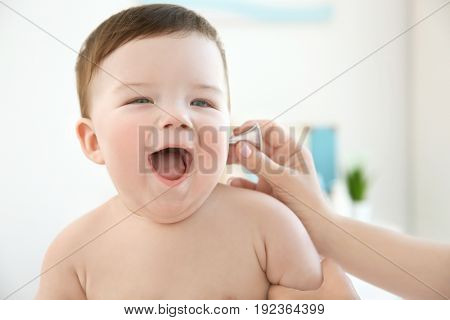 Doctor examining little baby with ear speculum in clinic. Baby health concept