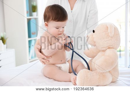 Cute little baby playing with stethoscope and toy at doctor's office. Baby health concept
