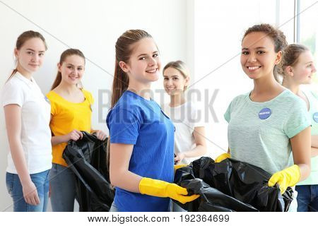 Young volunteers with garbage bags indoors