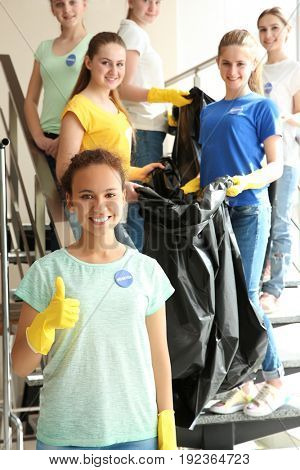 Team of young volunteers with garbage bags on staircase