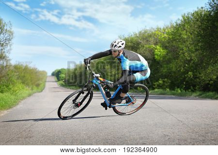 Sporty cyclist riding bicycle outdoors on sunny day
