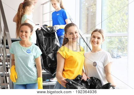 Team of young volunteers with garbage bags on staircase near window