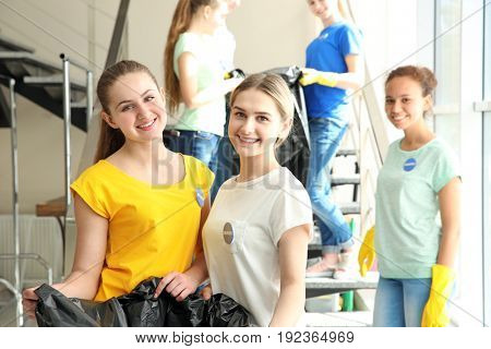 Young volunteers with garbage bags near staircase