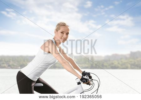 Young female cyclist riding bicycle near river