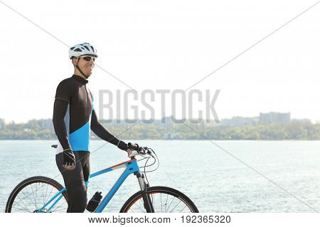 Sporty cyclist with bicycle near river