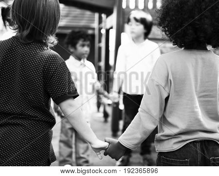 Group of diverse kindergarten students standing holding hands together
