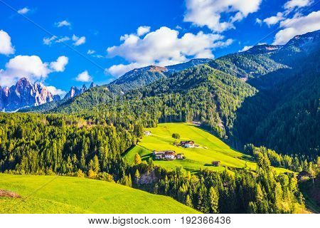 Charming chalet on a green grassy slope. The valley is surrounded by a dentate wall of dolomite rocks. Warm autumn in the Dolomites. The concept of ecological tourism