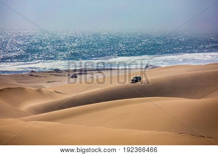 Atlantic coast of Namibia, south of Africa. Dangerous safari through the huge sand dunes on the ocean shore. The concept of exotic and extreme travel