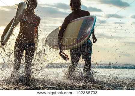 Couple of surfers run with boards and lots of splashes