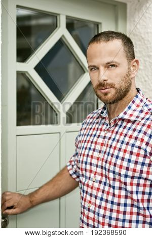 An image of a handsome man with a beard at the door