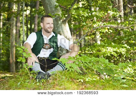An image of a traditional bavarian man in the green forest