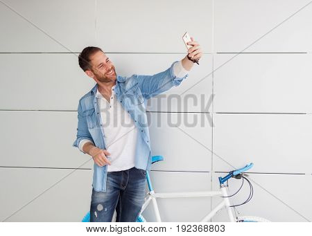 Casual guy with his vintage bicycle taking a photo with the mobile