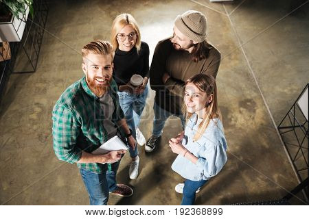 Picture of young colleagues in office talking with each other holding notebook. Looking at camera.