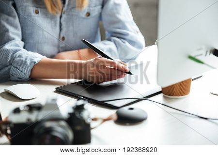 Cropped image of young woman work in office using computer and graphic tablet